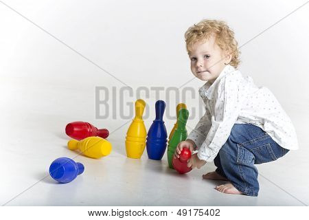 Toddler is playing with tenpins