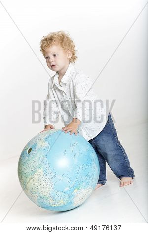Cute toddler is playing with a big globe