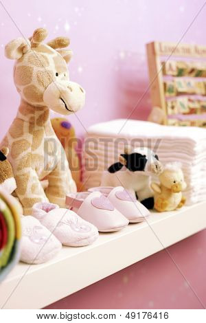 Stuffed toys shoes and nappies on shelf in baby's room