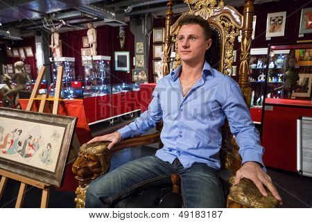MOSCOW - JAN 24: A man sits on a wooden throne in Museum-Shop Point G on Novy Arbat on January 24, 2013 in Moscow, Russia.
