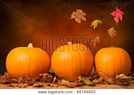 Three pumpkins with fall leaves with seasonal background