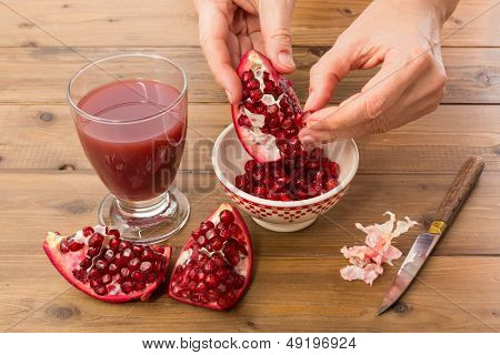 Hands of a woman collecting the seeds of a pomegranate