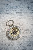 foto of cartographer  - Old compass on a cartographic map of mountains - JPG