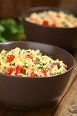 foto of tabouleh  - Fresh homemade Tabbouleh an Arabian vegetarian salad made of couscous tomato cucumber onion garlic parsley and lemon juice served in brown bowls on dark wood (Selective Focus Focus one third into the tabbouleh)