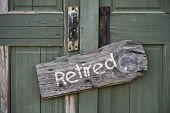 picture of retirement  - Old retired sign on green double door - JPG