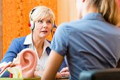 stock photo of earings  - Older woman or female pensioner with a hearing problem make a hearing test and may need a hearing aid - JPG