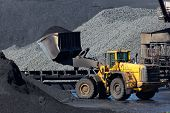 stock photo of power-shovel  - A yellow shovel moving brown coal around - JPG