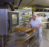 stock photo of trolley  - Female kitchen porter pushes a trolley of pastries - JPG