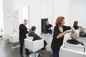 stock photo of barber  - Hairdressers giving haircut to customers in unisex salon - JPG
