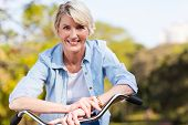 stock photo of mature adult  - close up portrait of senior woman on a bicycle - JPG