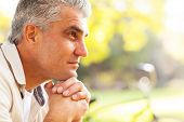 stock photo of daydreaming  - portrait of thoughtful middle aged man outdoors - JPG