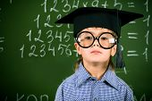 stock photo of diligent  - Portrait of a boy in round glasses and academic hat standing near the blackboard in a classroom - JPG