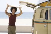 stock photo of camper-van  - Portrait of a mixed race man with surfboard on head by camper van - JPG