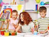 foto of kindergarten  - Children with teacher painting at easel in school - JPG