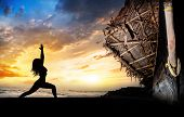 stock photo of virabhadrasana  - Woman silhouette doing virabhadrasana I warrior pose on the beach near the fisherman boat at sunset background in Varkala Kerala India - JPG