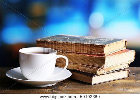 Cup of hot tea with books on table on bright background
