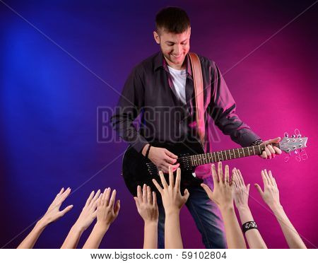 Guitarist singing on stage at a rock concert for his adoring fans