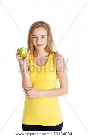 Beautiful causal caucasian woman holding fresh green apple with missing bite. Isolated on white.