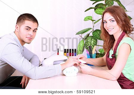 Beautiful girl manicurist doing manicure for man in beauty salon