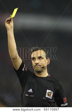 BARCELONA - JAN, 12: Referee Teixeira Vitienes delivers yellow card during Spanish soccer league match between Espanyol and Real Madrid at the Estadi Cornella on January 12, 2014 in Barcelona, Spain