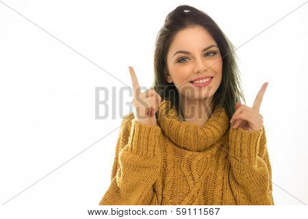 Beautiful brunette pointing above her head with both hands towards blank white copyspace as she draws your attention to a promotion