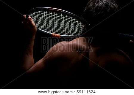 Tennis player and his racket highlighted on black background