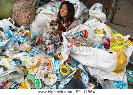 KATHMANDU, NEPAL - DEC 19: Unidentified child is sitting while her parents are working on dump, Dec 19, 2013 in Kathmandu, Nepal. In Nepal annually die 50,000 children, in 60% of cases -malnutrition.