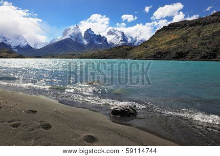 Sandy Beach Lake Pehoe in the national park Torres del Paine, Chile. Majestic rocks Los Kuernos. The beach is trampled by big traces