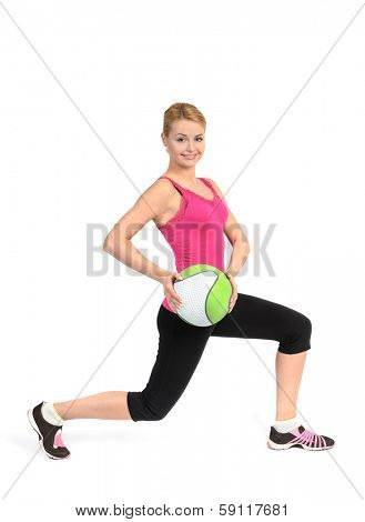 Young girl doing lunges exercise with medicine ball