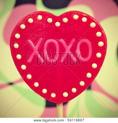 picture of a heart-shaped lollipop with the text XOXO, hugs and kisses, written in it, with a retro effect