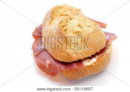 closeup of a spanish bocadillo de jamon serrano, a serrano ham sandwich, on a white background
