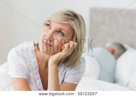 Closeup of a tensed mature woman sitting in bed with man in background at home