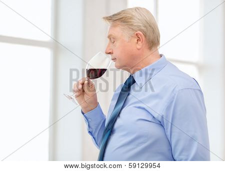 alcohol and beverage concept - older man smelling red wine