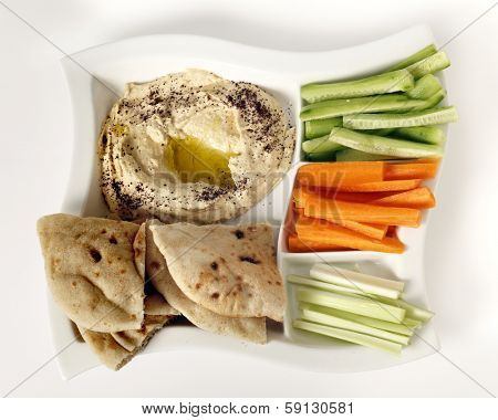 Top view of a dip tray with hummus, bread, carrot sticks, celery and cucumber.