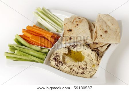High angle view of a dip tray with hummus, bread, carrot sticks, celery and cucumber.