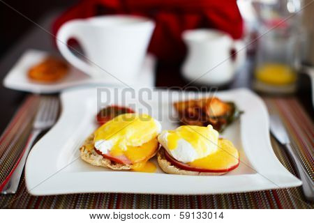 Delicious breakfast with eggs Benedict, vegetables, orange juice and coffee