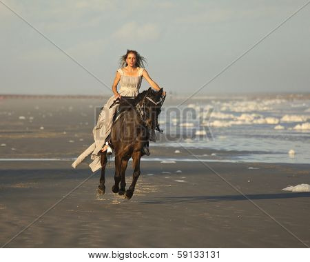 woman in medieval dress riding arabian horse on beach