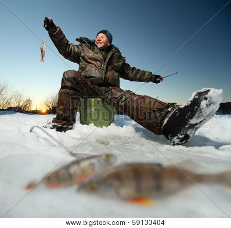 Happy fisherman on a lake at winter sunny day with fish