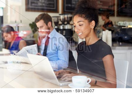 Businesswoman Using Laptop In Coffee Shop