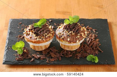 two home made muffins with chocolate on a slate cutting board