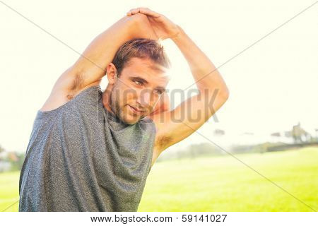 Attractive fit young man stretching before exercise workout, sunrise early morning backlit. Healthy lifestyle sports fitness concept.