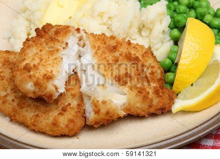 Breaded haddock fillets with mash and peas.