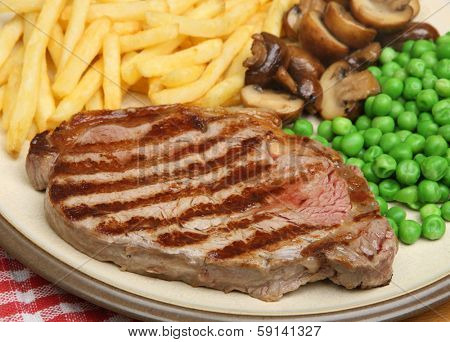 Sirloin beef steak dinner with fries, mushrooms and peas.