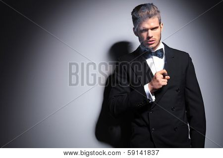 elegant man in suit and neck bow smoking a cigar against gray studio background