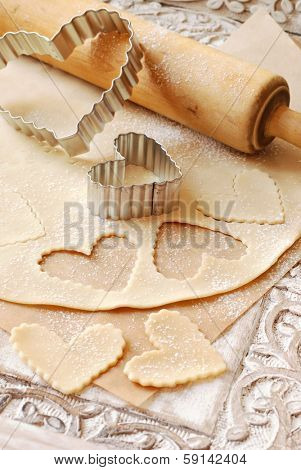 Heart shaped cookie cutters with dough and vintage rolling pin (dusted with flour) on rustic wood tray with carved design.
