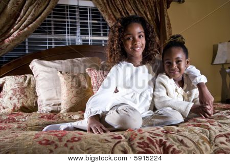 Two little sisters sitting side by side on a bed
