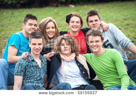 Group of highschool students posing outside in a park