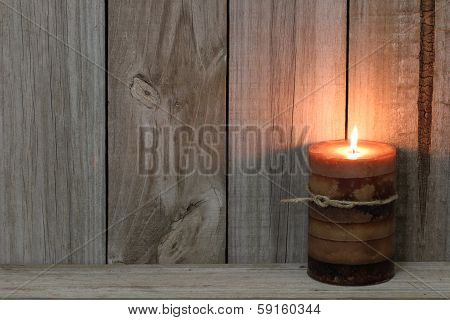 Textured burning candle by wood background