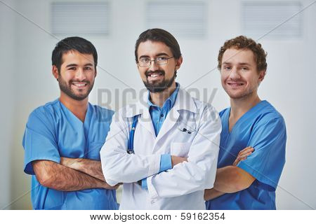 Portrait of three clinicians in uniform looking at camera