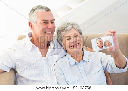 Smiling senior couple taking self portrait through smart phone at home